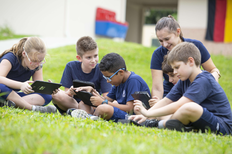 professora e alunos crianças estudando com tablet no gramado